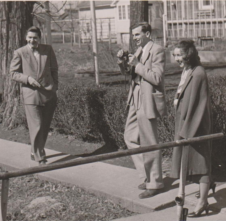 Czarno-białe zdjęcie dwóch mężczyzn i kobiety na dworzu