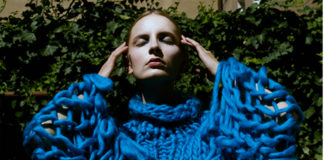 Dziewczyna w błętkinym swetrze na tle ściany porośniętej bluszczem