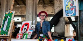 Dziewczyna stojąca przy stoliku z obrazami