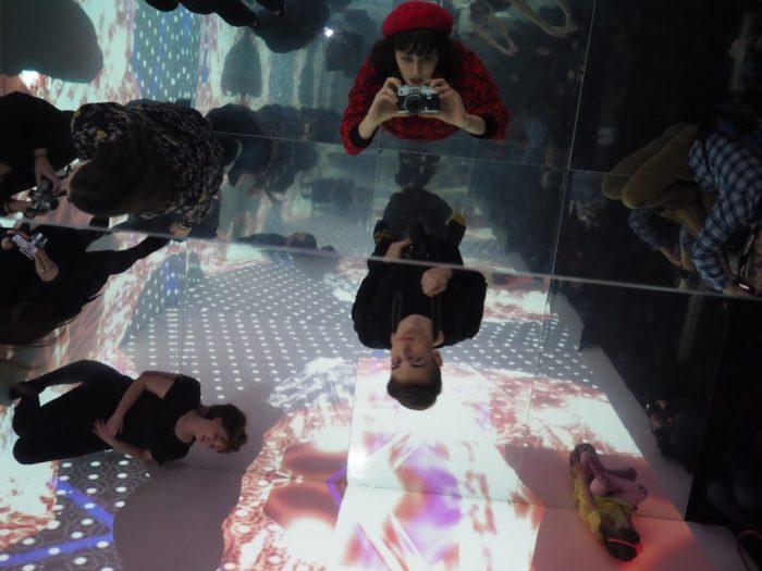dziiewczyna stojąca wśród ludzi robi zdjęcie sufitowi, na którym jest lustro- w nim też się obija