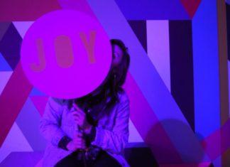 kolorystyka różowa, dziewczyna siedzi i trzyma przed twarzą tabliczkę z napisem JOY