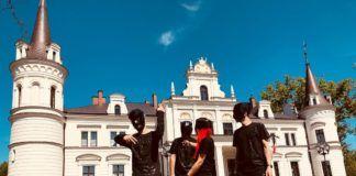Czworo ludzi w maskach stojących przed zamkiem
