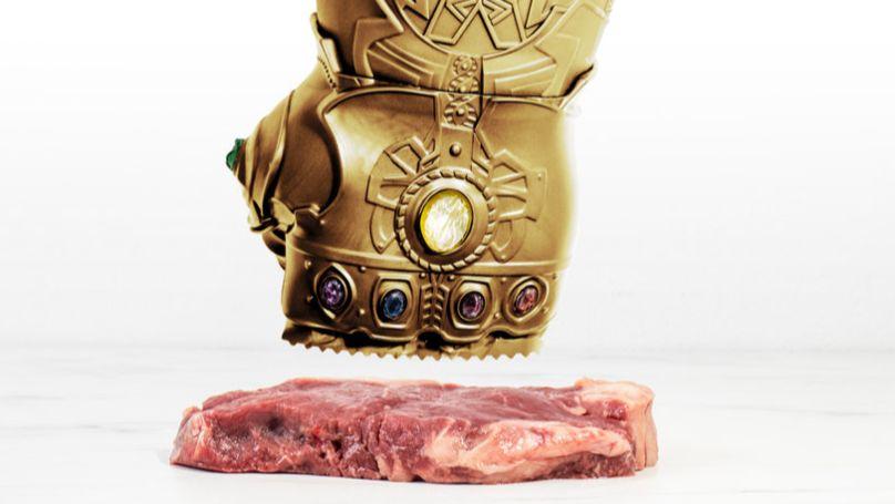 Złota rękawica do ubijania mięsa przy kawałku mięsa