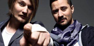 Dwóch mężczyzn pozujących do zdjęcia, jeden pokazuje palcem na aparat