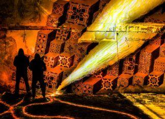 Mural na ścianie w kształcie pioruna i dwójka ludzi stojąca obok