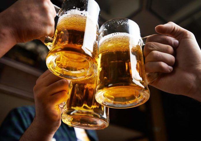 Trzy dłonie trzymające trzy kufle z piwem