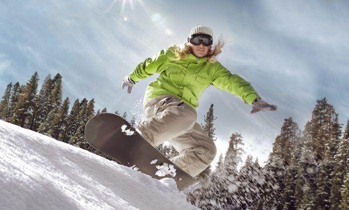 Dziewczyna w zielonej kurtce na snowboardzie