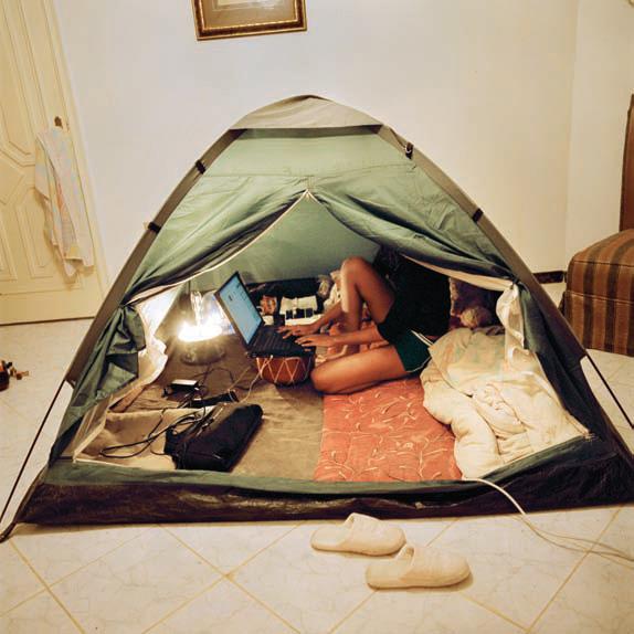 Kobieta siedząca z komputerem w namiocie