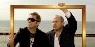Dwóch mężczyzn trzymających złotą ramkę