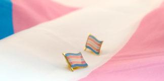 Przypinki flagi transpłciowej leżące na fladze