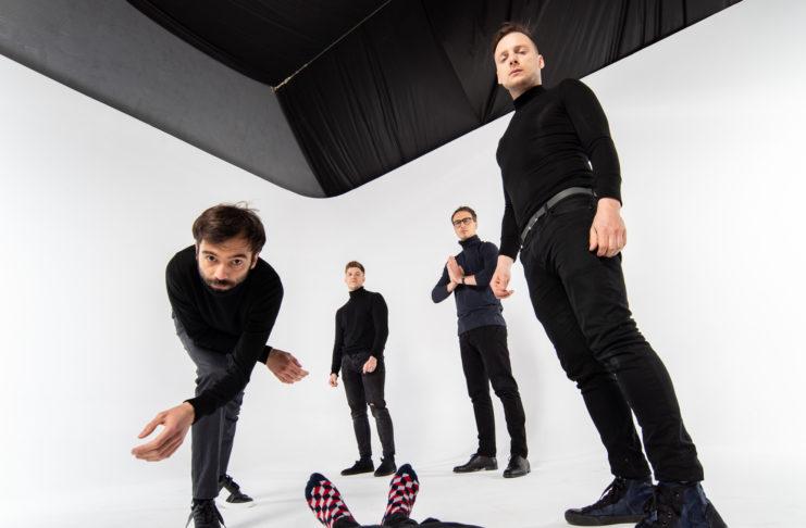 Czterech mężczyzn na białym tle uchwyconych od dołu