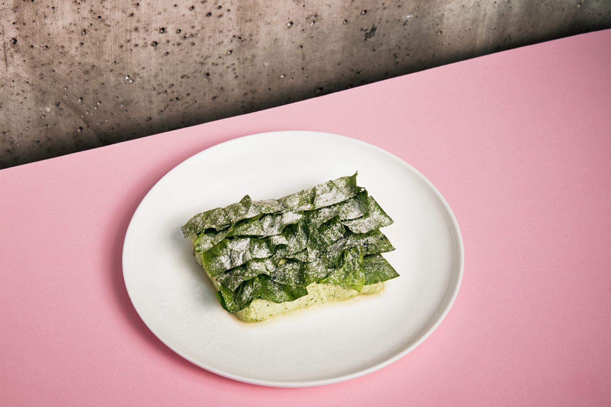 Danie na białym talerzu na różowym tle