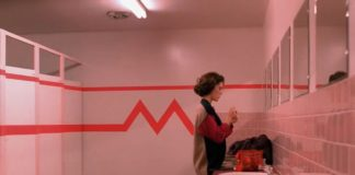 wnętrze łazienki i dziewczyna stojąca przy lustrze