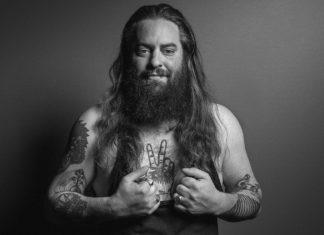 Czarno-białe zdjęcie mężczyzny z długi włosami, bez koszulki