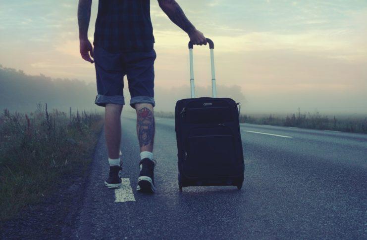 Mężczyzna z walizką idący wzdłuż drogi