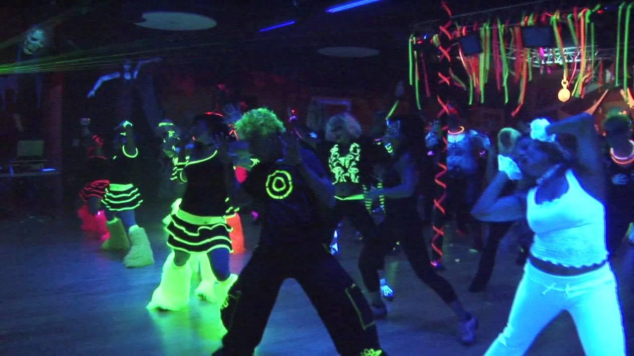 Ludzie ubrani we fluorescencyjne ubrania bawiący się na imprezie