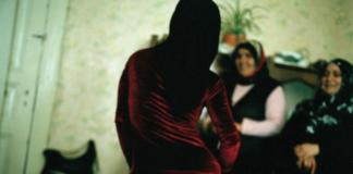 Trzy kobiety, jedna odwrócona tyłem w czerwonej sukience