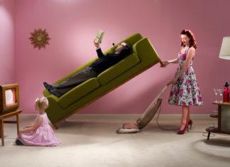 Zdjecie przedstawiajace mezczyzne lezacego na kanapie i kobiete odkurzajaca