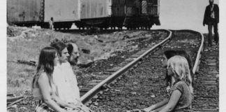 Czarno-białe zdjęcie ludzi siedzących na torach