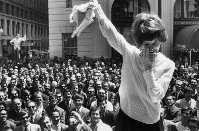 Kobieta trzymająca w rękach stanik, w tle tłum ludzi