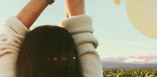 Dziewczyna odwrócona od obiektywu, patrząca na pole słonecznikow