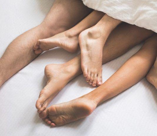 Trzy pary nóg pod kołdrą