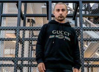 Mężyczyzna na tle barierek w czarnej bluzie Gucci