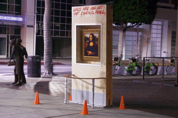Obraz Mony Lisy zawieszony w betonowej ścianie na środku ulicy