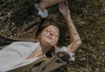Dziewczyna w białej koszuli, leżąca na trawie