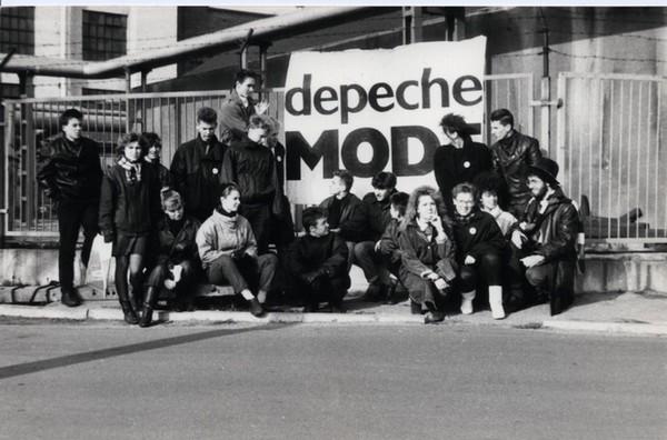 czarno-białe zdjęcie przedstawiające grupę ludzi ubranych w czarne ramoneski, którzy stoją na tle baneru z napisem Depeche Mode