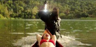 Kobieta dryfująca na łódce i ciemna postać wynurzająca się z wody