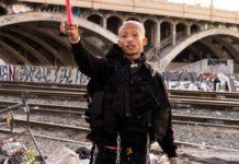 Chłopak ubrany na czarno w różowych włosach z uniesioną lewą ręką
