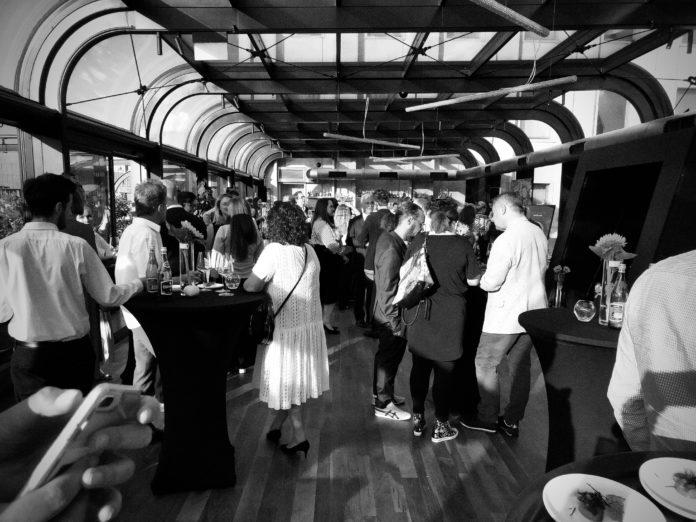 Czarno-białe zdjęcie przedstawiające ludzi na przyjęciu