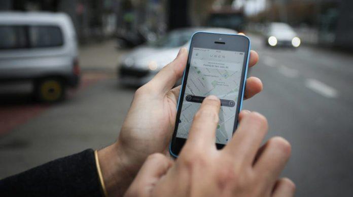 Dłoń trzymająca smartfon z otwartą aplikacją Uber