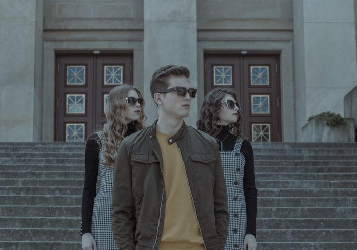 Dwie dziewczyny i jededn chłopak stojący przed budynkiem