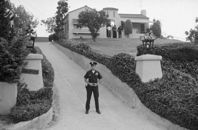 Czarno-białe zdjęcie pokazujące policjanta stojącego przed willą