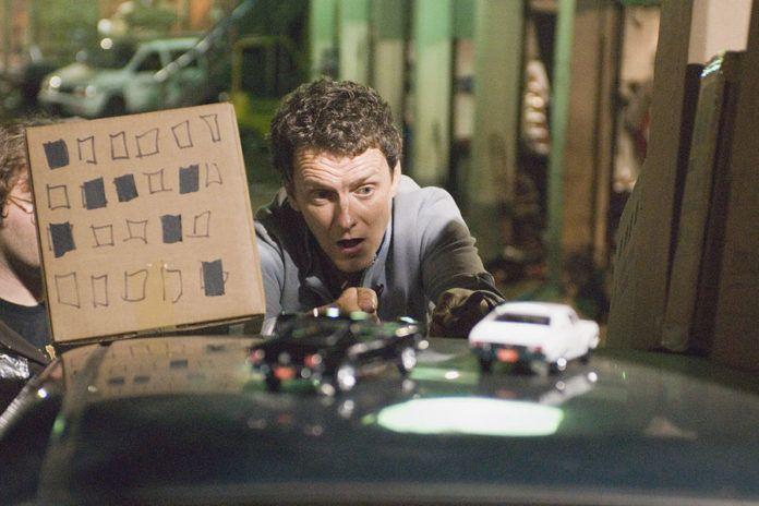 Mężczyzna opierający się o blachę samochodu