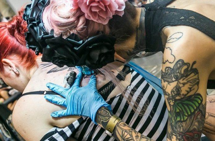 Dziewczyna tatuująca drugą dziewczynę