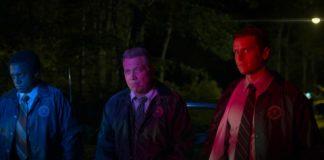 Trójka mężczyzn oświetlona światłem radiowozu