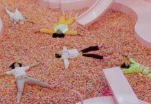 Ludzie leżący w basenie wypłenionym tęczową posypką