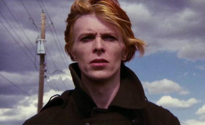 Rudowłosy mężczyzna z rozwianymi włosami, w tle błękitne niebo