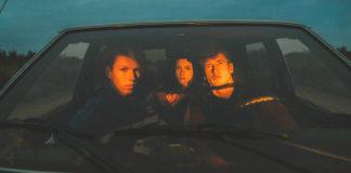 Dwóch chłopaków i dziewczyna siedzący w samochodzie