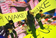 Czterech mężczyzn ubranych w czarne garnitury. Jeden śpiewa do mikrofonu, dwóch gra na gitarach, jeden na perkusji. Wokół nich kolorowe ekrany z napisami.
