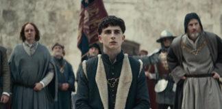 Kadr z filmu The King, w centrum siedzi ubrany w średniowieczny strój Timothee Chalamet, grający główną postać księcia Hala