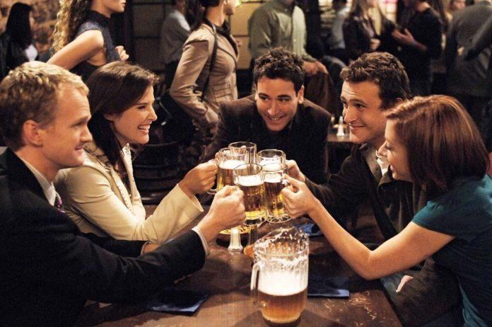 Grupa przyjaciół świętująca przy stole z toastem