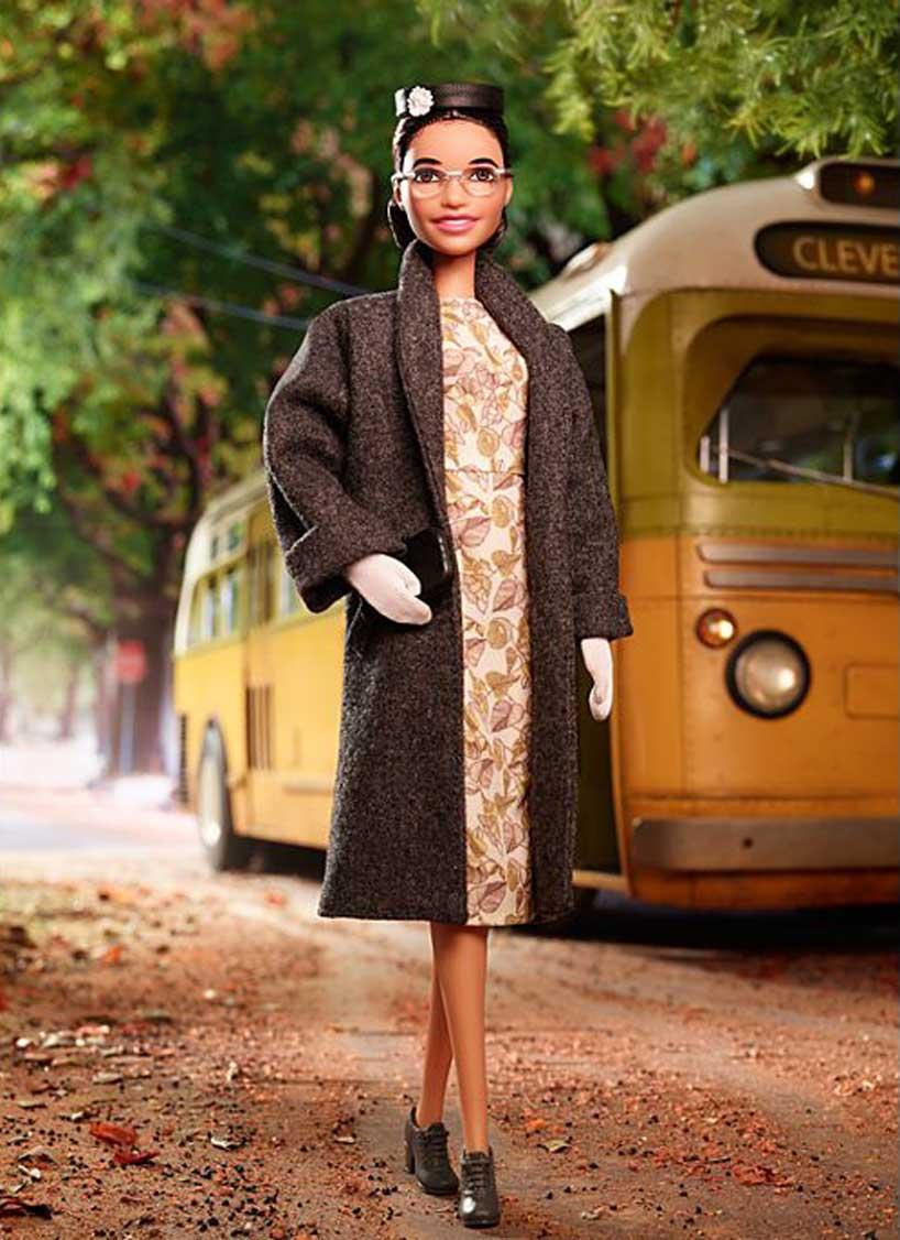 Zdjęcie przedstawiające lalkę ubraną w płaszczyk i sukienkę z lat 50. ucharakteryzowana na Rosę Park, amerykańską działaczkę. W tle jej symbol rozpoznawczy autobus.
