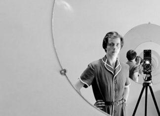 Czarno-białe zdjęcie kobiety stojącej przy lustrze
