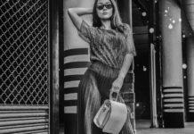 Czarno-białe zdjęcie przedstawiające kobietę trzymającą torebkę