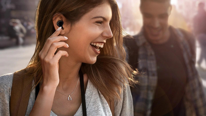 Uśmiechnięta dziewczyna z bezprzewodowymi słuchawkami w uszach