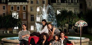 Grupa ludzi siedzaca na kanapie przy fontannie
